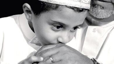 طفل يقبل يد والده