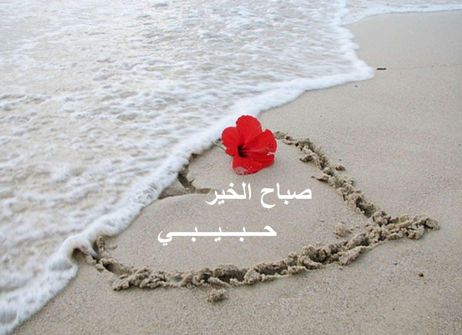 قلب مرسوم على شاطئ و مكتوب فيه صبياح الخير حبيبي.