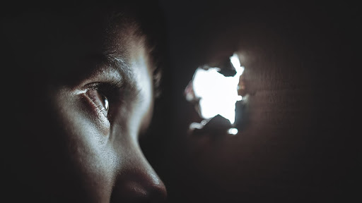 طفل صغير يبكي و ينظر من ثقب.